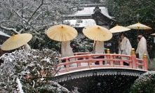 ** CORRECTS SPELLING OF ALTARS IN THE FIRST SENTENCE ** Shinto priests proceed to one of altars for new year's prayer under snow fall at the Kamigamo shrine in Kyoto, Japan, Sunday, Jan. 7 2007. Kyoto, former capital of the country for over 1200 years, retains thousands temples and shrines and local residence of centuries old as well as life style of tradition. Throughout the first two weeks of the new year, the city shows spirit and legacy of tradition they have long protected. (AP Photo/Junji Kurokawa)